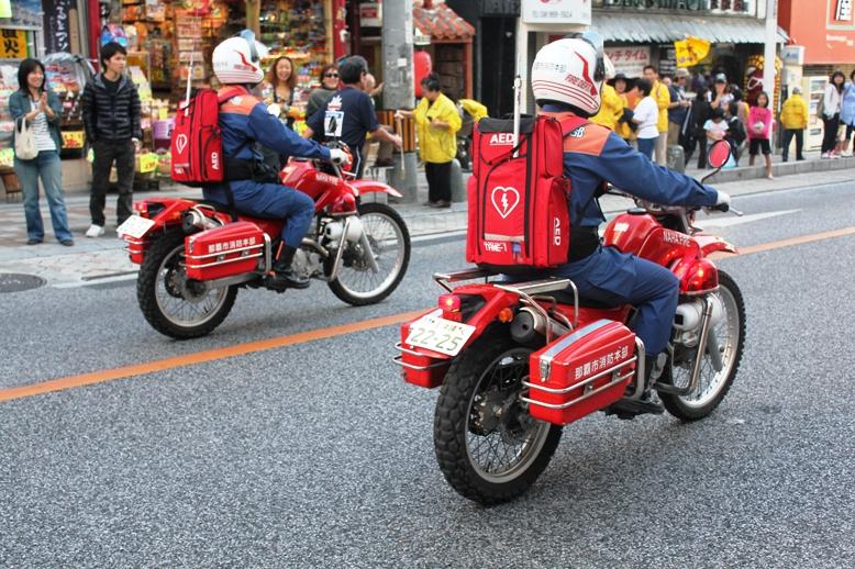 赤バイクにライドオンする隊員の背に緊急事態に備えてAEDが